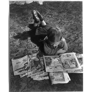 Child lying on floor with comic books,little boy Home